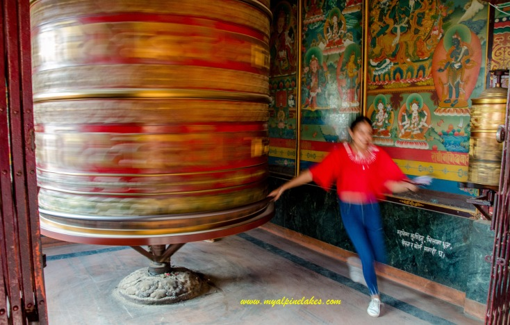 A young Nepali girl loves this oversize prayer wheel
