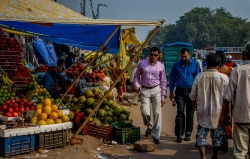 Businessmen strolling through a busy produce market.