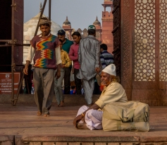 A man pondering about life in front of the busy mosque