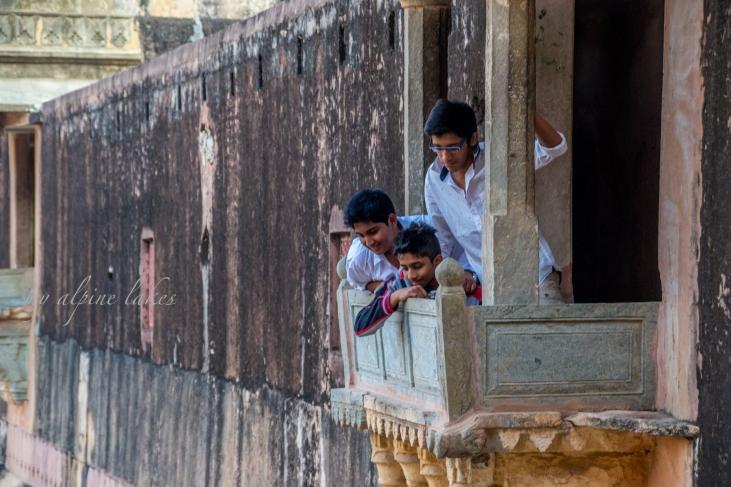 Boys holler at their friends below a balcony