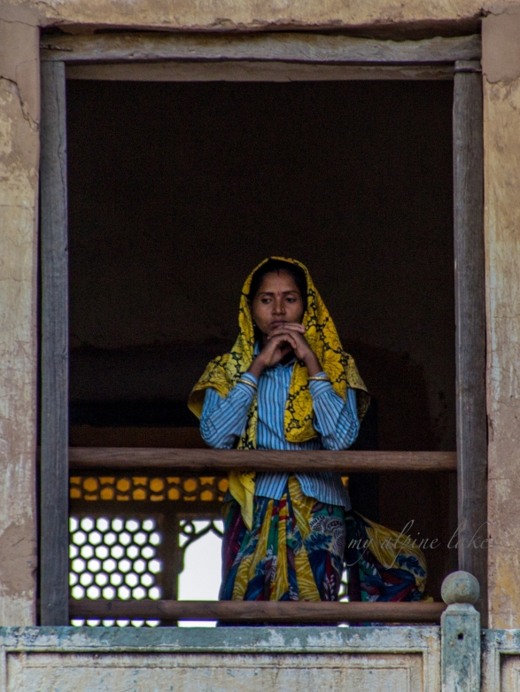 A woman deep in her thoughts in front of a window in Jaipur castle