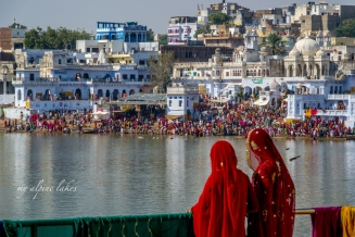 Two ladies in red shawl looking across the lake at the crowded bathing ghats.