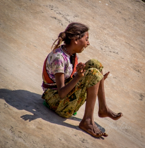 A young girl was thrilled to slide down a concrete river bank. Pushkar.