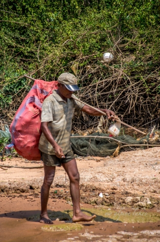 A man picking up plastic bottles along the shore of Tonle Sap