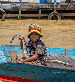 Interesting kid holding up a large snake while riding back on a dinghy. It turns out taking a picture of him required some money.