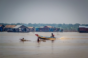 Villagers travel between houses on little motorized dinghy
